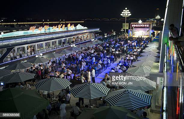 This photo taken on August 12 2016 shows a general view of guests attending the opening of the Pyongyang Taedonggang Beer Festival on the banks of...