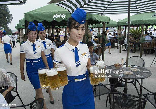 This photo taken on August 12 2016 shows a waitress carrying jugs of beer to guests before the opening of the Pyongyang Taedonggang Beer Festival on...