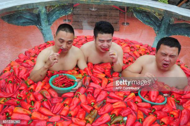 This photo taken on August 12 2017 shows competitors eating chili peppers while taking a chili bath during a chili pepper eating competition in...