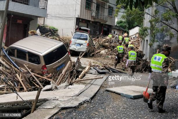This photo taken on August 12, 2019 shows rescuers working in the aftermath of Typhoon Lekima in Linan in China's eastern Zhejiang province. - The...