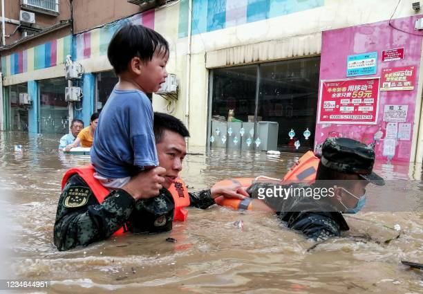 This photo taken on August 12, 2021 shows rescuers evacuating a child from a flooded area following heavy rains in Suizhou, in China's central Hubei...