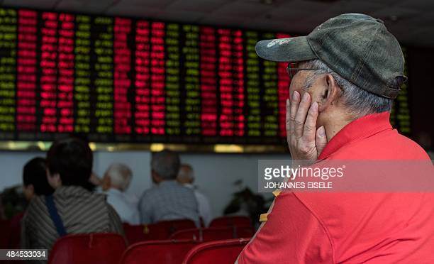 This photo taken on August 13 2015 shows investors monitoring screens showing stock market movements at a brokerage house in Shanghai Shanghai stocks...