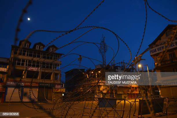 TOPSHOT This photo taken on August 14 2016 shows a barbedwire fence during a curfew in Lal Chowk in Srinagar on August 14 part of tightened security...
