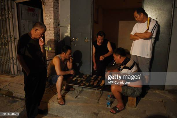 This photo taken on August 14 2017 shows men playing Chinese chess in an alley in Beijing The International Monetary Fund is scheduled to release its...