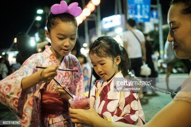 This photo taken on August 14 2017 shows Miyu Yamamoto eating shaved ice with syrup with her sister Riko during the Awa Odori festival in Tokushima...