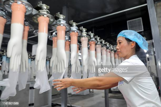 This photo taken on August 14, 2019 shows an employee working on a medical glove production line at a factory in Huaibei in China's eastern Anhui...
