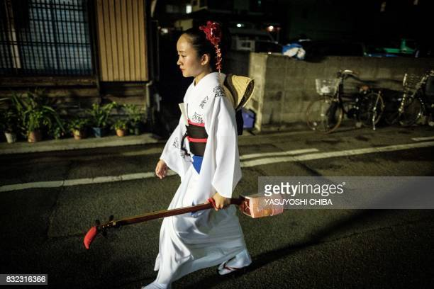 This photo taken on August 15 2017 shows a musician walking with a shamisen a Kapanese threestringed instrument during the Awa Odori festival in...