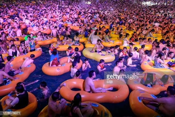 This photo taken on August 15, 2020 shows people watching a performance as they cool off in a swimming pool in Wuhan in China's central Hubei...