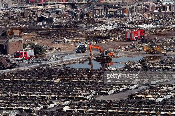 This photo taken on August 16 2015 shows rescue vehicles behind rows of burnt out cars at the site of the explosions in Tianjin Chinese staterun...