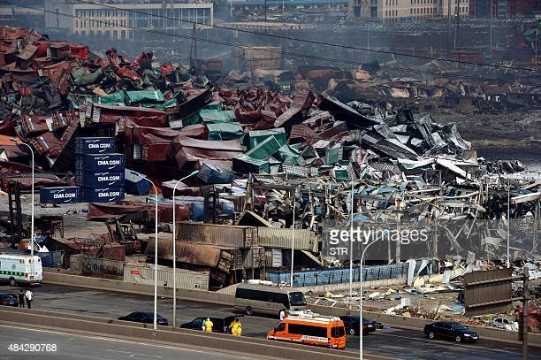 This photo taken on August 16 2015 shows rescuers working as mangled cargo containers and wreckage are seen at the site of the explosions in Tianjin...