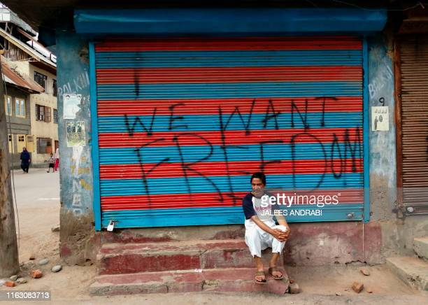 TOPSHOT This photo taken on August 16 2019 shows a man sitting next to graffiti that reads We Want Freedom on a shuttered store in the Soura locality...
