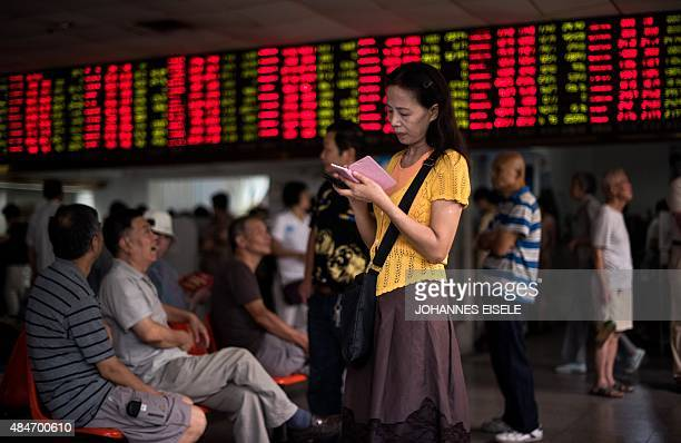This photo taken on August 18 2015 shows investors monitoring screens showing stock market movements at a brokerage house in Shanghai Shanghai stocks...