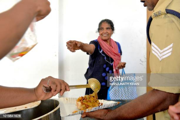 This photo taken on August 19 2018 shows an Indian woman getting food at a relief camp for flooddisplaced people in Chalakudi Taulk in Thrissur...