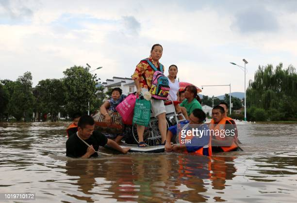 This photo taken on August 19, 2018 shows rescuers evacuating residents through floodwaters after heavy rainfall caused by Typhoon Rumbia in Huaibei...