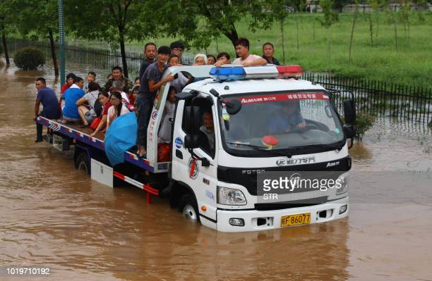 This photo taken on August 19, 2018 shows rescuers evacuating residents with a truck through floodwaters after heavy rainfall caused by Typhoon...