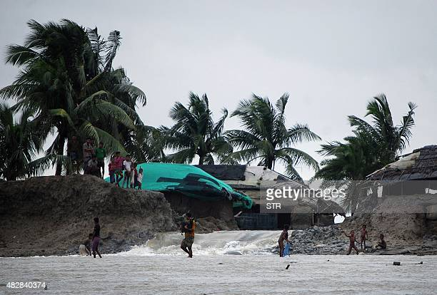 This photo taken on August 2 2015 shows Bangladeshi villagers walking through flood waters in Cox's Bazar The area was hit by heavy rains brought to...