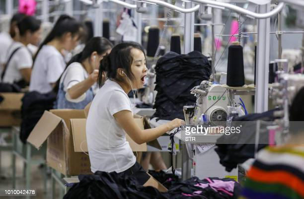 This photo taken on August 2, 2018 shows workers at a swimwear factory in Yinglin town in Jinjiang, in China's eastern Fujian Province. - China's top...