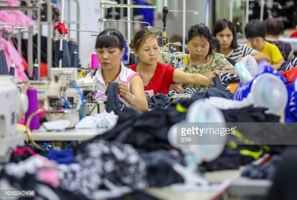 This photo taken on August 2 2018 shows workers at a swimwear factory in Yinglin town in Jinjiang in China's eastern Fujian Province China's top...