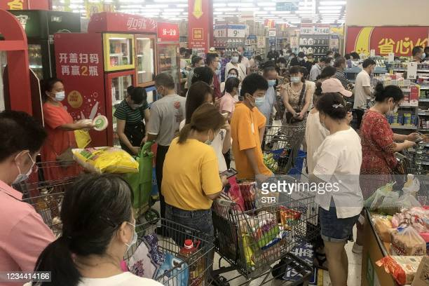 This photo taken on August 2, 2021 shows people buying items at a supermarket in Wuhan, in China's central Hubei province, as authorities said they...