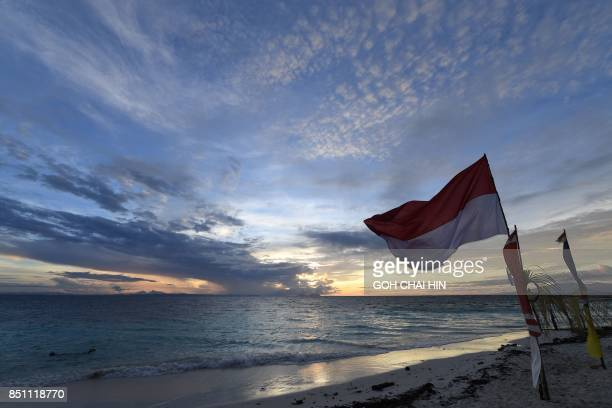 This photo taken on August 20 2017 shows the Indonesian national flag fluttering in the wind during sunrise in Raja Ampat which means Four Kings in...