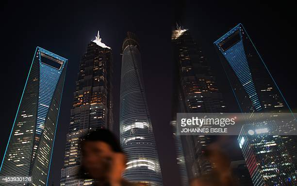 This photo taken on August 21 2014 in Shanghai shows a woman walking on a bridge in front of Shanghai's skyscrapers and its reflections Shanghai...