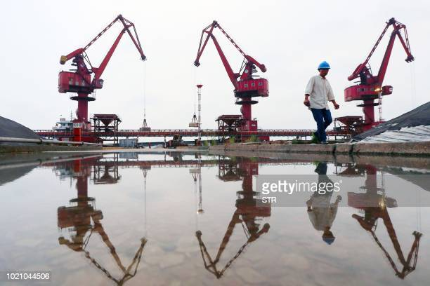 This photo taken on August 21 2018 shows a worker walking as crane buckets transfer soybeans imported from Brazil at a port in Nantong in China's...
