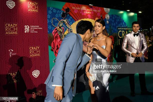 This photo taken on August 21 2018 shows Australian actor Chris Pang greeting Liv Lo wife of BritishMalaysian actor Henry Golding at the premier of...