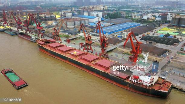 This photo taken on August 21 2018 shows crane buckets transferring soybeans imported from Brazil on a cargo ship at a port in Nantong in China's...