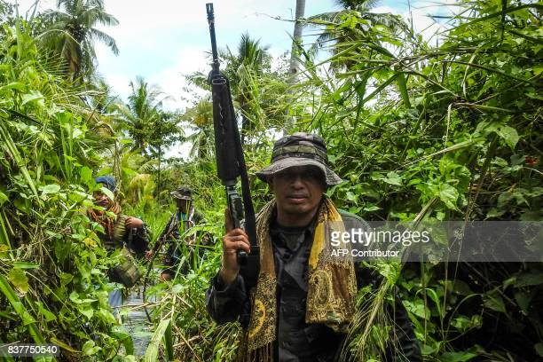 This photo taken on August 22 2017 shows a government police officer along with members of the Moro Islamic Liberation Front wading through a flooded...