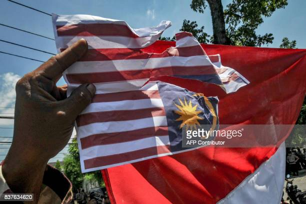 This photo taken on August 22 2017 shows protesters tearing burning and holding upsidedown a replica of the Malaysian national flag during an...