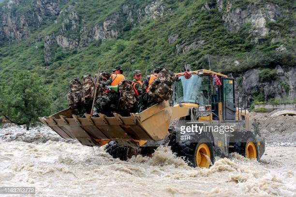 This photo taken on August 22, 2019 shows a bulldozer carrying Chinese paramilitary police officers as they head to a site of a mudslide caused by...