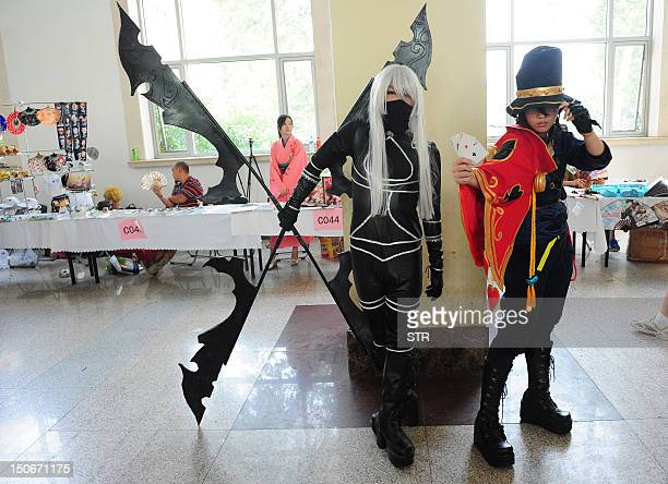 This photo taken on August 23 2012 shows 'cosplay' fans posing for photographs during the fourday 2012 Animation and Comics Fair at the National...