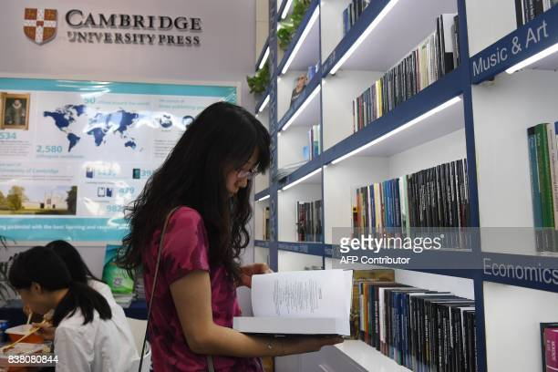 This photo taken on August 23 2017 shows a woman reading a book at the Cambridge University Press stand at the Beijing International Book Fair in...