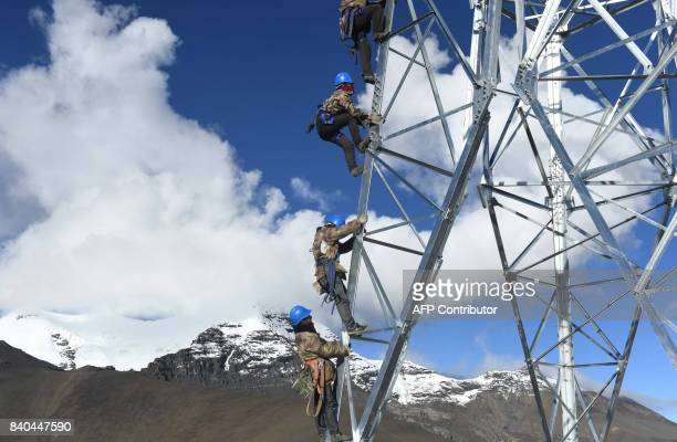 This photo taken on August 23 2017 shows Chinese workers climbing on a power transmission tower built at an attitude of 5548 meters on Mengdala...