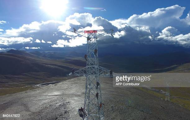 This photo taken on August 23 2017 shows Chinese workers on a power transmission tower built at an attitude of 5548 meters on Mengdala mountain in...