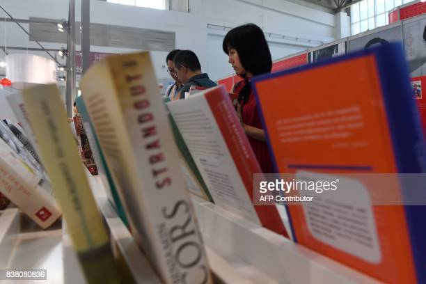 This photo taken on August 23 2017 shows people reading books at the Beijing International Book Fair in Beijing Just days after an outcry over an...