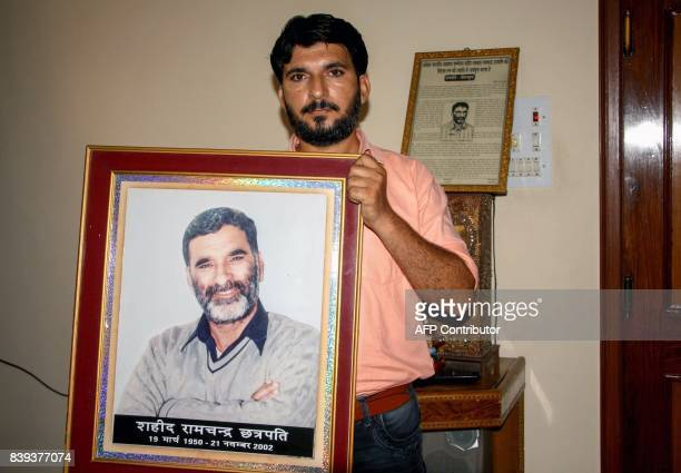 This photo taken on August 25 2017 shows Indian journalist Anshul Chhatrapati with a portrait of his father Ram Chander Chhatrapati who controversial...