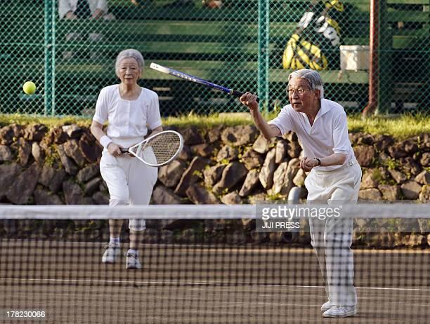 This photo taken on August 27 2013 shows Japanese Emperor Akihito and Empress Michiko playing tennis at Japan's mountain resort Karuizawa in Nagano...