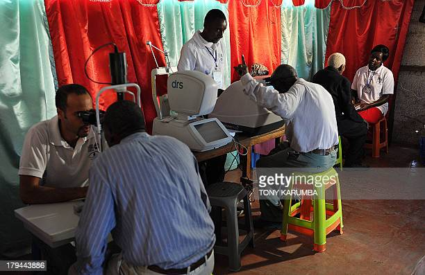 This photo taken on August 28 in Kianjokoma village near Kenya's lakeside town of Naivasha shows men being tested as they take part in an...