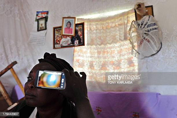 This photo taken on August 28 in Kianjokoma village near Kenya's lakeside town of Naivasha shows a technician scanning the eye of Mary Wambui at her...