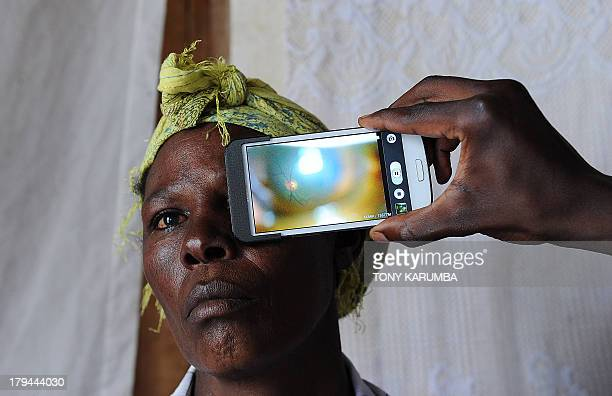This photo taken on August 28 in Kianjokoma village near Kenya's lakeside town of Naivasha shows a technician scanning the eye of a woman with a...