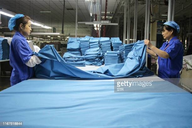 This photo taken on August 29 2019 shows workers folding cloth that will be exported to the US at a textile factory in Binzhou China's eastern...