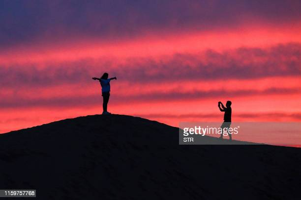 This photo taken on August 3, 2019 shows tourists taking photos as they visit the Kubuqi Desert in Baotou in China's northern Inner Mongolia region....