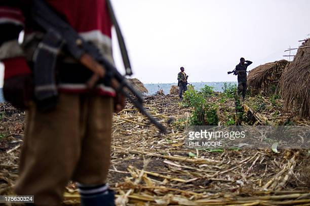 This photo taken on August 3 shows a Mai Mai Nyatura fighter standing guard with an AK-47 rifle near huts at a hilltop base in Kiseguro, around 90km...