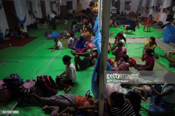 This photo taken on August 30 2017 shows ethnic Rakhine children who escaped from unrest taking a rest at a temporary shelter in Sittwe Rakhine State...