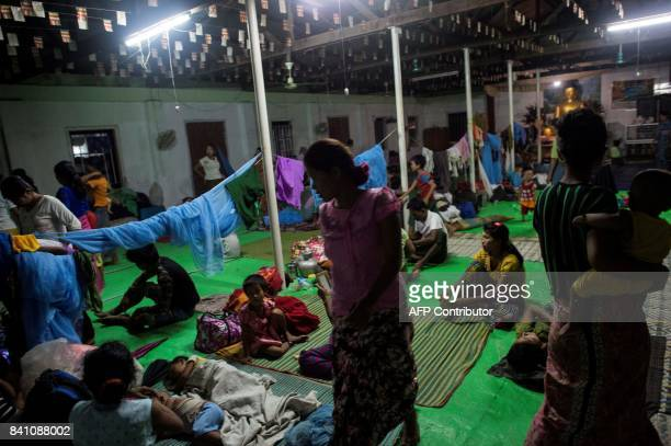 This photo taken on August 30 2017 shows ethnic Rakhine people who escaped from unrest taking a rest at a temporary shelter in Sittwe Rakhine State...