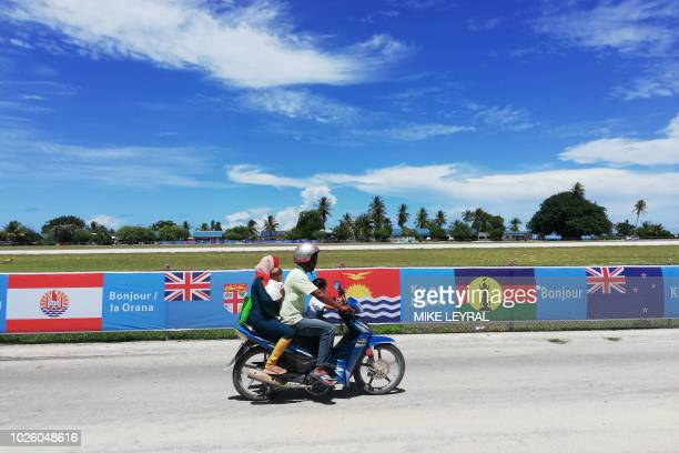 This photo taken on August 30 2018 shows a motorbike riding past flags set out ahead of the Pacific Island Forum in Yaren on the Pacific island of...