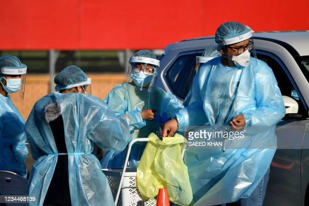 This photo taken on August 4, 2021 shows health workers taking swab samples from residents at a Covid-19 drive-through testing site in western Sydney...