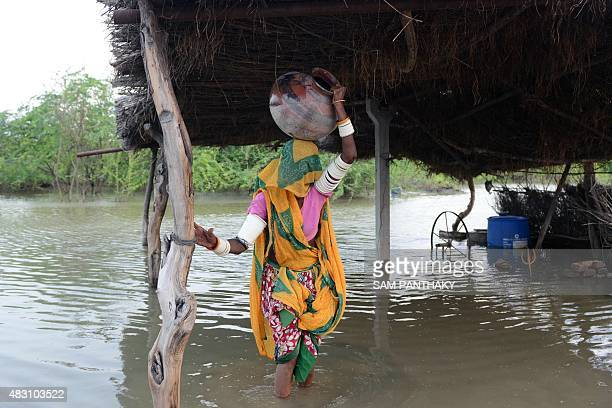 This photo taken on August 5 2015 shows an Indian woman carrying a pot on her head next to her flooddamaged home in Koreti village in Banaskantha...