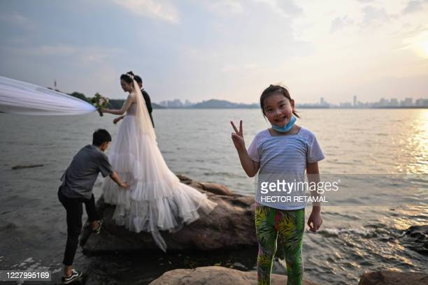 This photo taken on August 5, 2020 shows a girl gesturing while a couple pose for a wedding photographer next to East Lake in Wuhan in Chinas central...